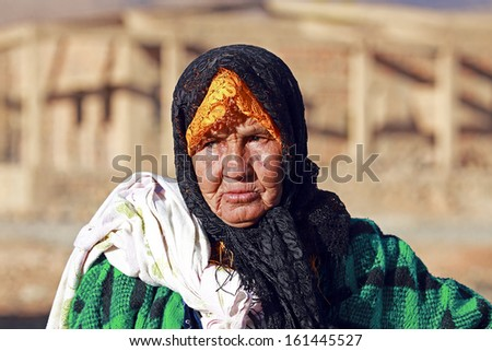 An old nomad woman in the desert - stock photo
