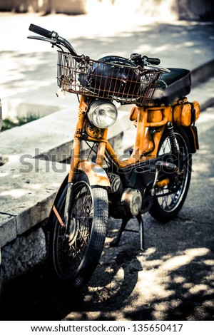 an old orange scooter with a rusty basket parked on the curb - stock photo