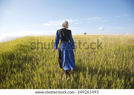 An Old Order Amish woman in a blue dress and black cape and apron walks in a grassy field on a sunny afternoon - stock photo
