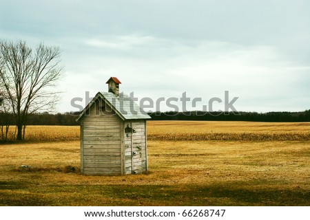 An old outhouse in the middle of an autumn field. - stock photo
