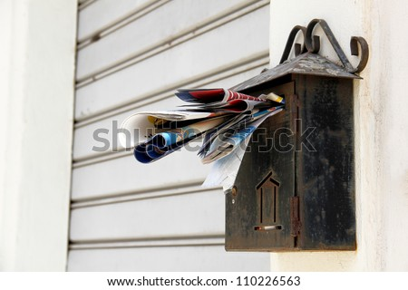 An old overloaded rusty mailbox waiting for someone to relieve if from the mail - stock photo