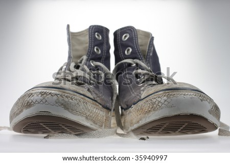 An old pair of trendy canvas shoes with a shallow depth of field - stock photo