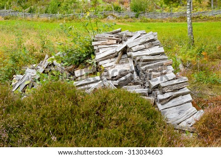 An old pile or stack of firewood found by the side of a farmers field in summer. Heather grow around the stack.  - stock photo