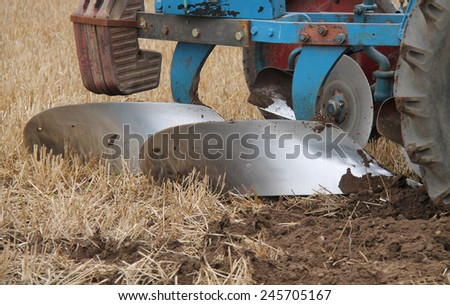 An Old Plough Cutting a Furrow in a Farmers Field. - stock photo