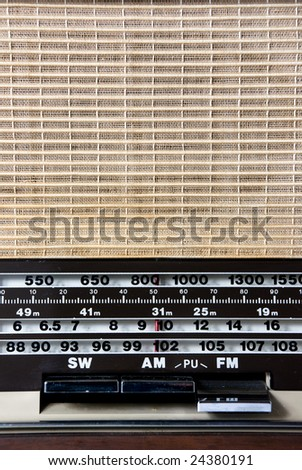 An old radio with a clothe speaker cover and tuning numbers with FM button pressed down. - stock photo