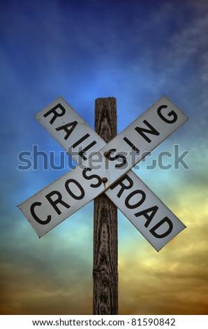 An old railroad crossing sign in front of a dramatic sunset sky. - stock photo
