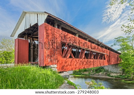 An old red covered bridge in Scipio, Indiana crosses Sand Creek under a blue cloudy sky. - stock photo