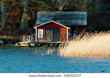 An old red, wooden boathouse with a small jetty in front. Reed and water in foreground and forest in background. Wind is bending the reed. Late December in Jarnavik bay outside Ronneby, Sweden. - stock photo