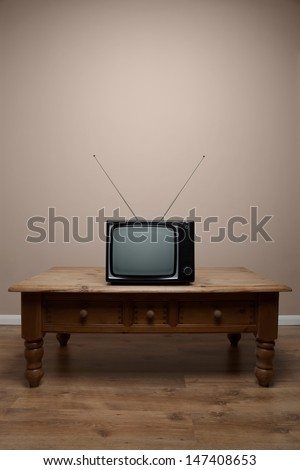 An old retro TV on a table with blank screen in an empty room, clipping path provided for the screen to add your own image or text. - stock photo