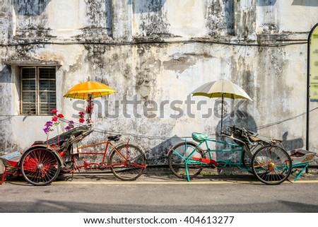 An old rickety trishaw cab parked on the sidewalk of a dilapidated building in Penang, Malaysia. - stock photo