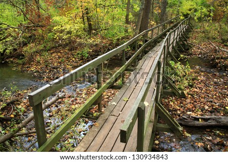 An Old, Rickety Wooden Foot Bridge Over A Stream In A Forest Ablaze With The Colors Of Autumn, Glen Helen Nature Preserve; Yellow Springs Ohio, USA - stock photo