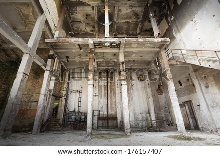 an old ruined abandoned industrial building interior - stock photo