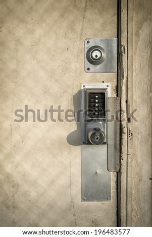 An old, run down wooden door with multiple locks and a keypad entry security lock. - stock photo