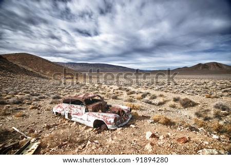 An old, rusted car sits under cloudy skies in Death Valley National Park, California. - stock photo