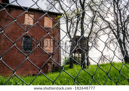 An old rusty metal fence locks up the property of abandoned camp building - stock photo