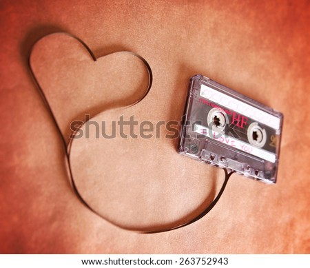 an old scratched up audio cassette tape in the shape of heart (focus on the words) on a brown paper texture background good for valentine's day or love greeting cards (SHALLOW DOF) - stock photo