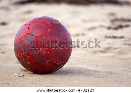 An old soccer ball/football on sand at the beach. - stock photo