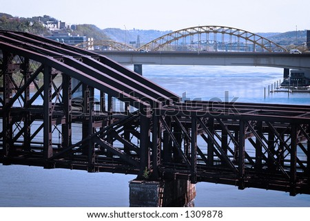 An old steel train bridge crossing a river. Taken in Pittsburgh, PA. - stock photo