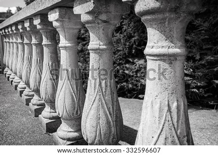 An old stone balustrade in perspective. Black and  white photo. Soft selective focus and shallow depth of field - stock photo