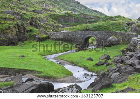 An old stone bridge carries a narrow road across the winding Serpent River in the rocky terrain near the Gap of Dunloe, famous tourist destination near Killarney, County Kerry, Ireland. - stock photo