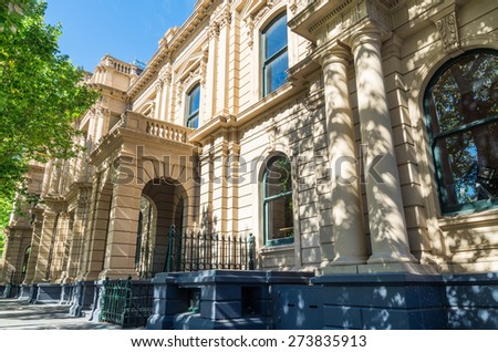 An old stone building with cream or sandstone coloured render. The building is surrounded by green trees and has numerous arched windows and doorways. - stock photo