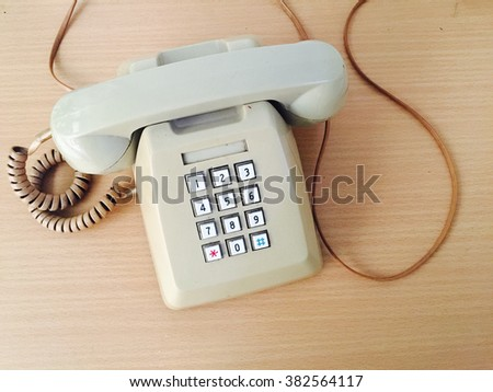 An old style digital telephone on wood table. - stock photo