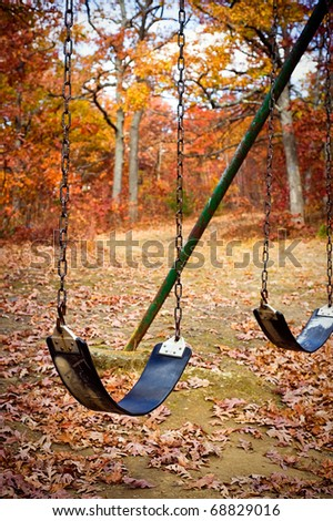 An old swingset in a park during the autumn season. - stock photo