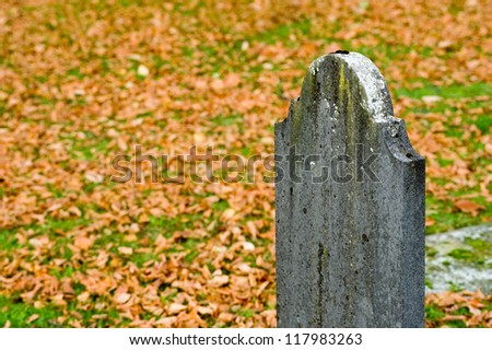 An old tombstone on a cemetery in the autumn - stock photo