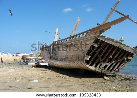 An old traditional Omani sail boat on the shore of the Fishing Village of Sur in Oman. - stock photo
