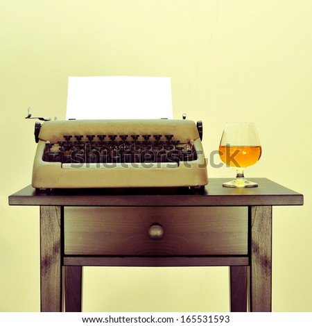 an old typewriter with a blank page and a brandy snifter with liquor on a desk, with a retro effect - stock photo