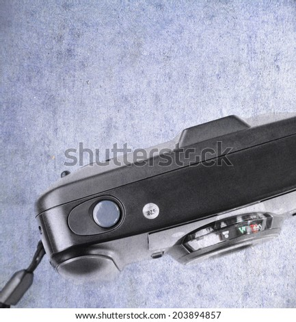 An old used film plastic camera over grunge background - stock photo