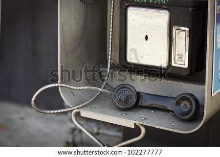 An old vandalized payphone left off the hook. - stock photo
