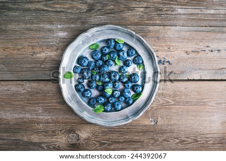 An old vintage metal plate full of fresh ripe blueberries over a rustic wooden desk background, top view - stock photo