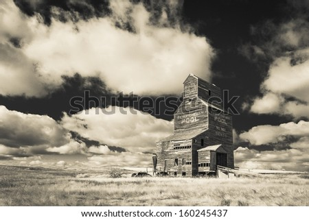 An old vintage wooden grain elevator in the ghost town of Bents, Saskatchewan.  Processed with an infrared filter. - stock photo