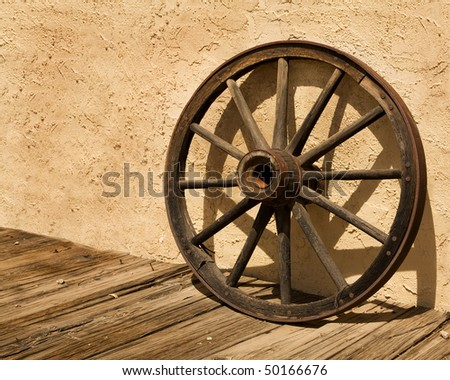 An old wagon wheel, an iconic symbol of the American West, sits on a wooden sidewalk and leans against a stucco wall.  It's a sunny day and the wheel casts an interesting shadow on the wall. - stock photo