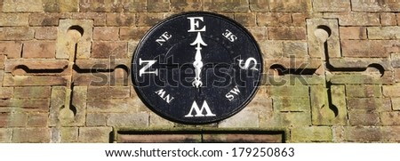 An old weather vane built into a stone wall. - stock photo