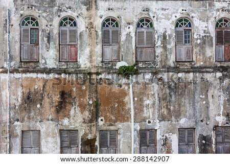 an old weathered neglected building wall with run down plaster and paint and old windows and shutters - stock photo