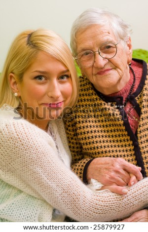 An old woman and her grandchild sitting close to each other (focus on the young woman) - part of a series. - stock photo