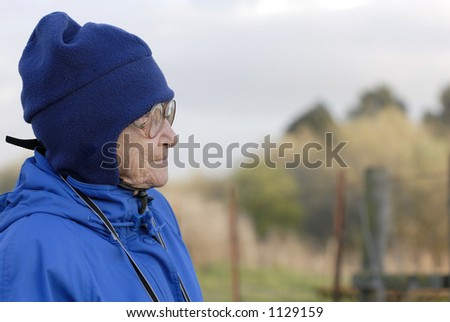 An old woman, bundled in a warm hat and jacket, stares off into the distance. - stock photo