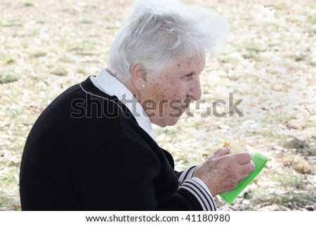 an old woman eating a slice of cake - stock photo