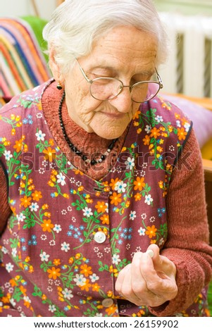 An old woman holding a pill in her hand - part of a series. - stock photo