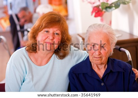 An old woman in a wheelchair in a nursing home with her daughter next to her, who came to visit her mother - other elderly peaople in the blurred background. - stock photo