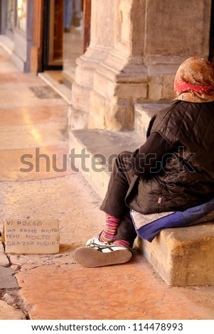 an old woman in the streets of Italy begging for some change - stock photo