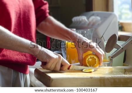 An old woman's hands peel citrus fruit to make fresh orange juice.Concept photo of mature woman, retire, retirement, lifestyle , health care, healthy lifestyle, healthy food, healthy drinks, fruits. - stock photo