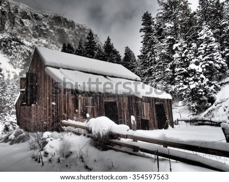 An old wooden barn in a snow storm. - stock photo