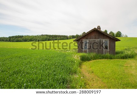 An old wooden barn in Sweden on a green vibrant pasture - stock photo