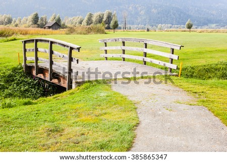 an old wooden bridge on an idyllic meadow or a beautiful golf course - stock photo