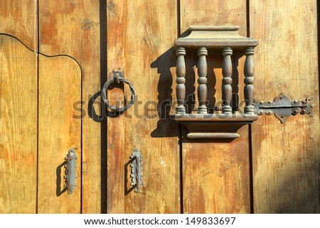 An old wooden door with metal yellow handles forged handmade. Antigua, Guatemala - stock photo