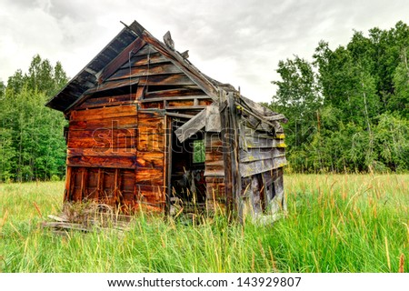 An old wooden shed in the middle of a field by the forest - stock photo