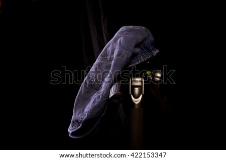 An old worn blue driver's cap against a black background. Hat is on camera tripod. - stock photo